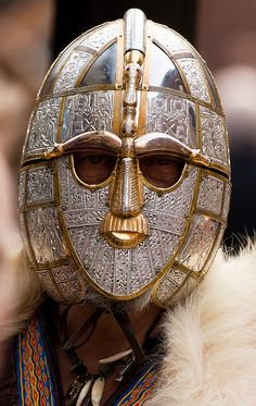 The Sutton Hoo burial site has been dated 7th century AD and is thought to be that of Rædwald ruler of the East Angles. Among the many treasures at the head of a suit of decorative mail armor was this iron helmet (replica) tin leaf and bronze were pure decoration. There is what appears to be a bird framing the eyes, nose and forehead.