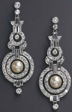 A PAIR OF ART DECO NATURAL PEARL AND DIAMOND EAR PENDANTS Each designed as an articulated series of diamond collet and baguette-cut diamond geometric links, the old European-cut diamond concentric circle pendant centering upon an independent pearl, measuring approximately 8.95 mm, mounted in platinum, circa 1930