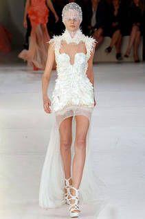 De la diseñadora británica Sarah Burton (jefa de la firma Alexander McQueen) este traje deja las piernas al descubierto. Resalta el tocado de la cabeza y los apliques puntiagudos que sobresalen de  el corpiño y hombros