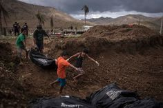 Bodies were placed in a mass grave on Thursday in Tacloban, Phillipines, six days after the city was largely destroyed by a typhoon