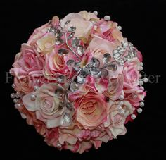 Kim,       A vibrant collection of coral, watermelon and apricot pink tones in a glamorous deep ball rose bouquet. Features silk royal roses, classic roses and duchess roses with a spray of mirrored crystals and scattered pearls. Bouquets handle is finished and bound in bridal white satin with silver studs. Measures 27cm across.