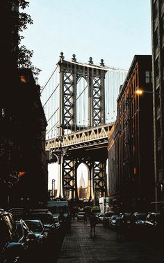 A view of DUMBO (Down Under the Manhattan Bridge Overpass) in Brooklyn, NYC. Here, the Manhattan Bridge lines up perfectly in the middle of two rows of houses, with the Empire State Building framed perfectly by the bridge. This guide shows you the best instagram spots in NYC! #newyork #nyctravel #newyorkcity #instagramguide #instagramtravelguide #travelguide #photography