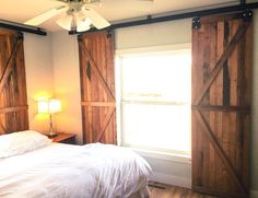 When our master bedroom needed window treatments, my husband made barn door window shutters that fit all my small space needs.