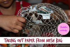 Taking paper out of the mesh bag! A simple problem solving activity for toddlers!