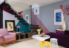 Para fugir da mesmice, o designer de interiores Moreno aproveitou as angulações da escada para conceber as geometrias na parede. Esboçou traços à mão e trabalhou com cores ousadas, como o vinho, o azul-acinzentado e o azul-carbono