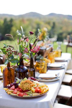 rustic flower and natural grass centerpieces in eclectic brown bottles | photo: www.kristynhogan.com