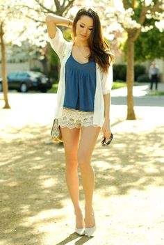 White lace shorts with blue top, white sweater, and nude heels.