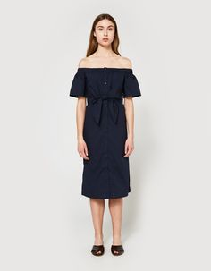 Modern mid-length dress from Farrow in Navy. Gathered elastic off-shoulder neckline. Short sleeves. Front button closure. Defined waist with wrap-look self-tie at front. Straight hem with side slits. Unlined.  • Percale • 100% cotton • Hand wash cold