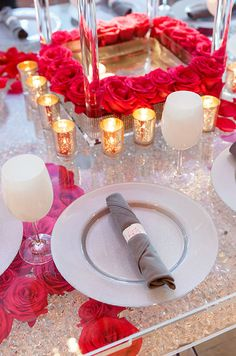 A metallic square tray is lined with red roses and surrounded by shimmering votive candles for a fabulously fresh look.