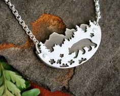 Wear your love of the outdoors with this unique mountain landscape necklace. Delicate hand cut details create a tranquil scene with a bear walking