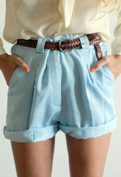 Cream blouse, ruffled blue shorts.