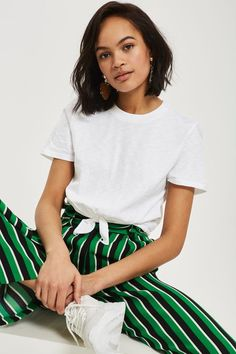 The t-shirt gets an update with our short sleeve design in white with a knot front at the hem. We're styling this versatile pair with colourful striped trousers for an effortless look.