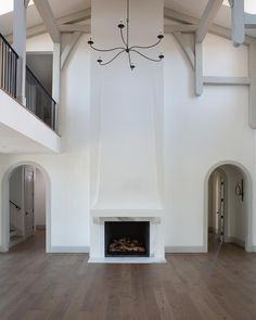 Jaimee Rose Interiors - Stunning 2 story living room features a two story fireplace boasting a marble surround and lit by a wrought iron chandelier hung from a gray truss ceiling. Two Story Fireplace, Home Fireplace, Living Room With Fireplace, Fireplace Design, Stucco Fireplace, Fireplace Remodel, Fireplaces, Living Room Remodel, Home Living Room