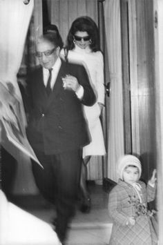Jacqueline Kennedy Onassis walking behind a Aristotle Onassis. -