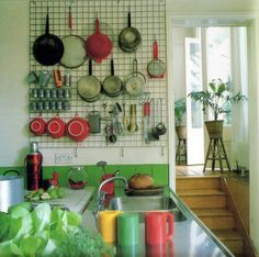 a different take on hanging pots and pans - Bright.Bazaar: {Kitchen: utilitarian chic} This is much better than my current storage method of having the big ones stacked on the counter. Kitchen Wall Storage, Kitchen Rack, Kitchen Storage Solutions, Kitchen Organization, New Kitchen, Kitchen Decor, Kitchen Design, Kitchen Pegboard, Kitchen Ideas