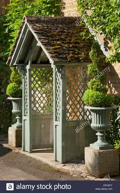 Download this stock image: wooden Porch with lattice sides of Cotswold cottage flanked by box spiral Topiary in stone urns, England - cr19ct from Alamy's library of millions of high resolution stock photos, illustrations and vectors.