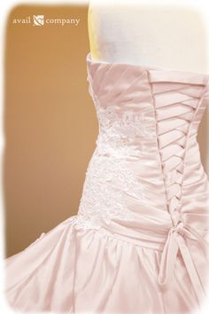 Blush Pink Wedding Dress - Angela Style - Avail & Company, LLC  This gorgeous dress is made of blush pink matte satin with a drop waist and ruched bodice. The dress displays bead work(clear beads and pearls) and lace. The back features corset styled lacing.  The dress also comes with attachable straps and a train.