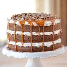 Epic Caramel Pecan Carrot Cake recipe with layers of fluffy filling, caramel drizzling down the sides and chopped pecans on top!