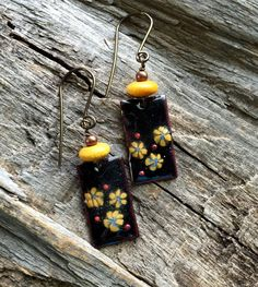 Copper rectangles are glass enameled in black. Yellow millefiori flowers were added and a goldenrod yellow wood bead sits on top. The earrings hang from non-allergenic Niobium earwires. Simple and classy.