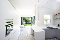 A side return extension to a Victorian cottage in Battersea Our client's brief was to transform the existing kitchen space into a light and spacious dining room and to create a generous family kitchen. The scheme blurs the boundary between inside and out. Kitchen Floor Tile Patterns, Kitchen Tiles Design, Kitchen Layout, Kitchen Flooring, Kitchen Ideas, Tile Design, Corner Bifold Doors, Conservatory Kitchen, White Gloss Kitchen