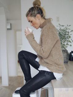 messy bun, soft tan turtleneck sweater, white pinstripe shirt, leather pants and ankle boots