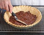 Thoroughbred Pie Recipe - Cook's Country | The majority of recipes for this classic chocolate-walnut-bourbon concoction produce pies that are far too sweet, so we wanted to rein in the sugar to get balanced flavor. For starters, we reduced the amount of sweetener to almost half what was called for in some recipes, and we replaced the semisweet chocolate chips with chopped bittersweet chocolate.