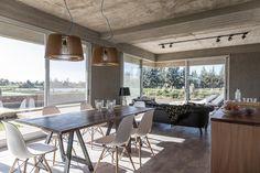 Living comedor con gran presencia de hormigón expuesto en una casa moderna.