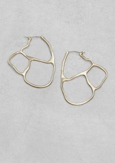 With an intriguing cutout design, these earrings are crafted from brass.