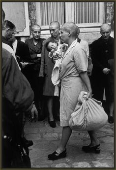Robert Capa - Chartres, France, August 18th, 1944: Just after the liberation of the town, this French woman who had had a baby with a German soldier has her head shaved as punishment.  During the middle ages, this mark of shame, denuding a woman of what was supposed to be her most seductive feature, was commonly a punishment for adultery. Shaving women's heads as a mark of retribution and humiliation was reintroduced in the 20th century and was widespread post WW2.