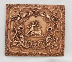 unknown artist - French or Bavarian style wall plaque depicting a winged figure holding a stag's antlers framed by an elaborate scrolled border