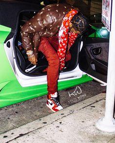 Travis Scott Hops Out A Lamborghini Wearing Supreme Playboy Jacket, Louis Vuitton x Supreme Scarf, Air Jordans and Cartier Bracelet  |  UpscaleHype