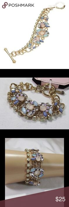 "JUICY COUTURE Chic Multi-Stone Toggle Bracelet NWT JUICY COUTURE stunning multi-stone toggle bracelet features sparkling simulated crystals! This chic toggle bracelet makes a unique fashion statement!  BRACELET DETAILS Length: 6.5 in. Closure: toggle Metal: gold tone Stones: clear, peach, mint, blue & purple simulated crystal *Matching Necklace & Earrings available in separate listing under ""Jewelry"" to be bundled & purchased!  *Bundle Discounts * No Trades * Smoke free Bird by Juicy Couture…"