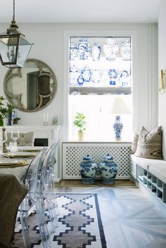 Blue and white porcelain vases and urns in dining space with antique mirror