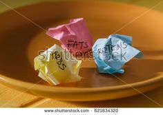 Conceptual image for nutrition: plate with paper pieces spelling carbs, fats and proteins.