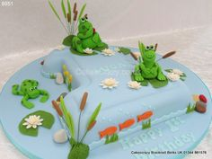 Large number one shaped cake in blue decorated with pond life of bulrushes and lilies, and finished with sugar modelled frogs First Birthday Parties, First Birthdays, Birthday Cakes, Frog Cakes, Pond Life, Number Cakes, Gum Paste, Fondant, Cake Decorating