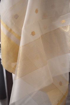 Handwoven silk-cotton Chanderi cream and gold saree hand-picked from the quaint town of Chanderi. Available at Omnah.