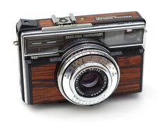 "The Vitessa 500 AE (electronic) is a 35mm camera with an electronic shutter, made in Germany from 1968-70. Aperture & shutter speed are visible in the finder.  This camera was available with the standard all-black look, or with the ""jacaranda wood"" look seen on this example."