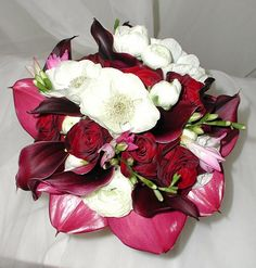 purple and red #bouquet featuring roses, ranunculus, calla lilies, freesia and anemones