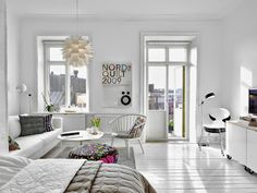 A perfect Swedish apartment for a spring day with an open space living area and a stack of Ant chairs from Fritz Hansen | you can never have enough chairs
