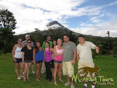 Guided tour group on a Costa Rican getaway trip posing in front of the Arenal Volcano with their guide... https://www.costaricamonkeytours.com/costa-rica-tour-33/