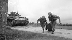 2/22/1968-Hue, South Vietnam: Two members of the First Air Cavalry drag a wounded GI across Highway 1, after being ambushed by Communist forces. The cavalrymen were moving south toward Hue when the attack occurred.