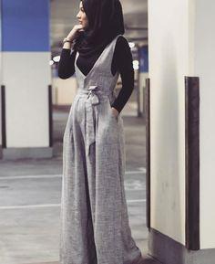 Grey jumpsuit, black shirt, black scarf, watch: