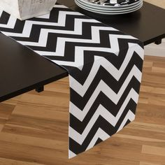 Features:  -Chevron collection.  -Material: 100% Cotton.  -Fits most tables.  -Machine washable.  -Line dry recommended to avoid shrinkage.  Material: -100% Cotton.  Pattern: -Chevron. Color Black/Whi