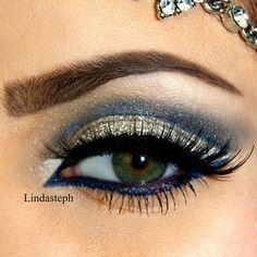 Shimmery gold & blue eyeshadow with dark blue underliner & fake lashes.