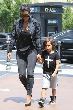 Kim Kardashian wearing Celine Matrix Top Heavy Sunglasses, J Brand Photo Ready Cropped Mid Rise in Mercy, Saint Laurent Paris Suede Pumps and Acne Studios Encore Shine Bomber Jacket in Black.