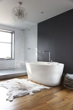 black and gray bathroom features tear drop chandelier over freestanding bathtub paired with floor-mounted tub filler paired with sheepskin rug placed in front of black accent wall and next to walk-in shower accented with glass shower partition and mosaic marble shower surround.