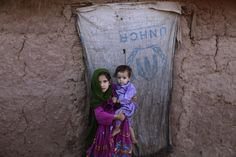 Afghan refugee girl Waleemah Syed, 7, holds her brother Marvaiz, 1, by the doorway of their home, on World Refugee Day, in a slum on the outskirts of Islamabad, Pakistan, Wednesday, June 20, 2012. AP / Muhammed Muheisen