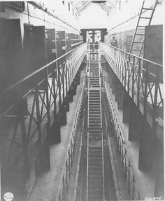 The interior of the Gestapo prison in Koeln.    Prisoners were forced to run these stairs while whipped by guards.  Prisoners stripped the paint from the doors where the American officer is standing as a result of going mad from Allied air raids.