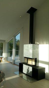 Fantastisk bild på eldstaden Contura i51T med värmelagrande täljsten och två vedfack i svart plåt. En modern kamin för moderna hem. Installerad av HBM Braskaminer.