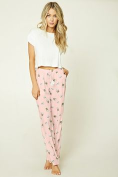 A pair of woven PJ pants featuring an allover coffee and donut print, slanted side pockets, a wide straight-leg design, elasticized waist, and a bow front with tassels.